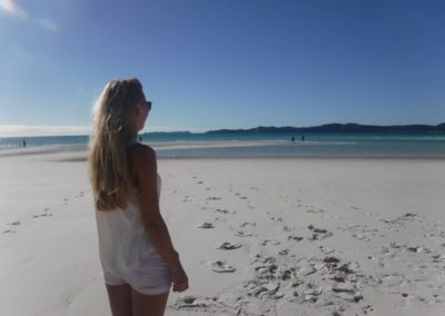 girl standing on the soft white sand